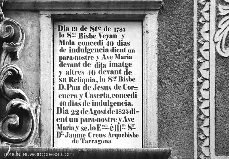 Text per aconseguir indulgències que hi ha a la façana de l'església barroca.