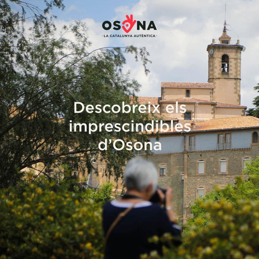 Imatge d'una dona fotografiant una església a la comarca d'Osona.